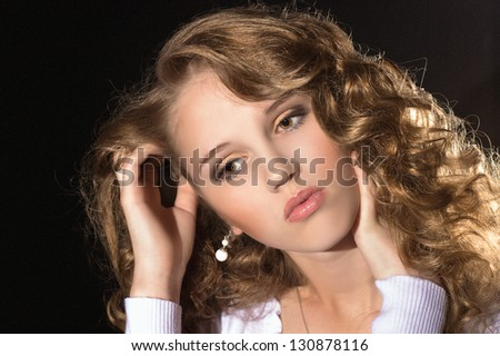 Beautiful curly-haired girl on a black background