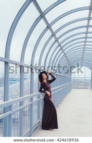 Beautiful curly-haired woman in a long dress on a light background