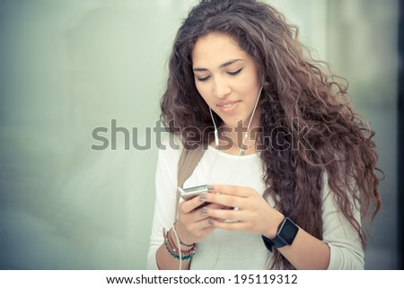 beautiful curly long brunette hair moroccan woman using smart phone in the city - stock photo
