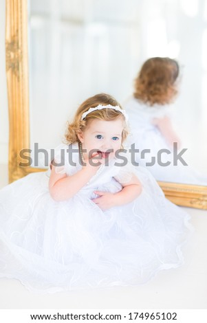 Beautiful curly toddler girl in a white dress sitting next to a big mirror - stock photo