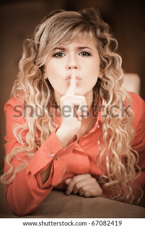 Beautiful curly young woman in red clothes calls for silence, putting forefinger to lips. - stock photo