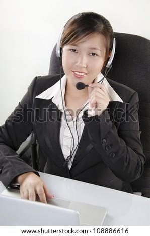 Beautiful customer service agent in call center - stock photo