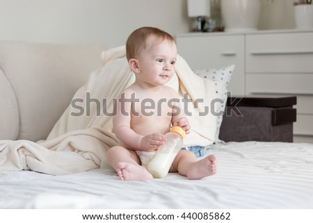 Beautiful cute baby in diapers sitting on bed with milk bottle - stock photo