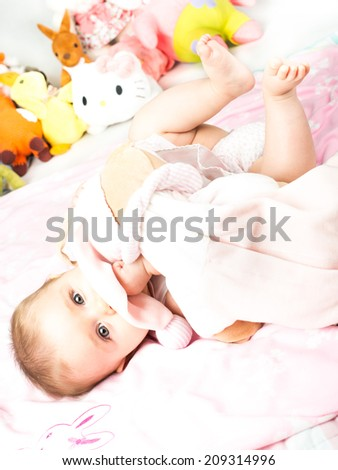 Beautiful cute baby with pink blankets and toys - stock photo
