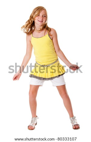 Beautiful cute blond girl having fun dancing fashion dressed in layered yellow shirt, white shorts and belt, isolated.