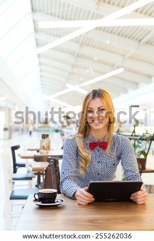 Beautiful cute girl in the cafe, holding a tablet and smiling. Enjoying her free time