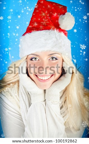 beautiful cute girl smiling in a red santa hat and falling snowflakes on a blue background