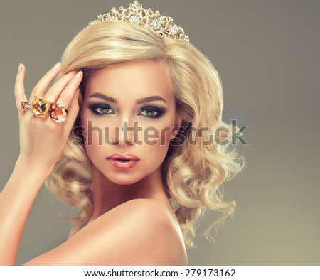 Beautiful cute girl with blonde curly hair with  the tiara on her head and large rings on her  hand - stock photo