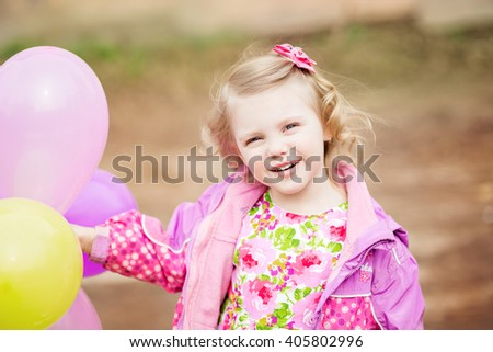 beautiful, cute little blonde girl with blond curly hair in a pink gingham dress jacket and rubber boots, laughing with balloons on walk, early spring / late autumn - stock photo