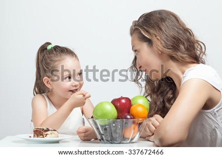 beautiful cute little girl convinced her mother to eat cake - stock photo