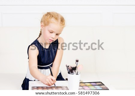 Beautiful, cute little girl playing with make-up palette. Family, home concept.