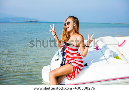 Beautiful cute sexy cheeky hipster blonde girl near a speed boat, wrapped in a scarf with a print of the American flag, lifestyle trendy sunglasses healthy tanned skin, hair, full lips, crazy emotions