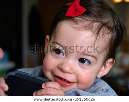 Beautiful cute toddler girl baby playing a smartphone - stock photo