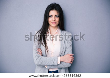 Beautiful cute woman with arms folded standing over gray background - stock photo