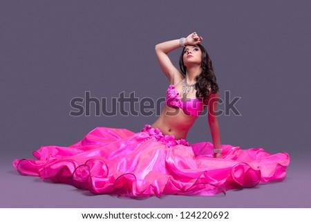 Beautiful dancer in pink costume  sitting on floor - stock photo
