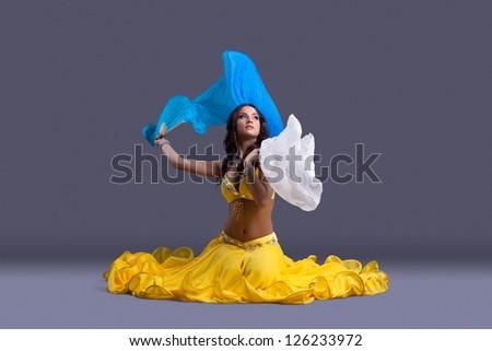 Beautiful dancer in yellow costume sit on floor - stock photo