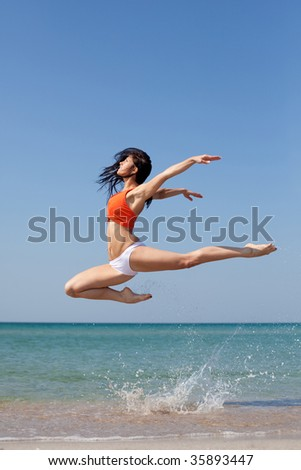 beautiful dancer posing on the sandy sea beach - stock photo