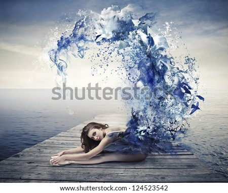Beautiful dancer with a blue dress that becomes a wave of blue paint - stock photo