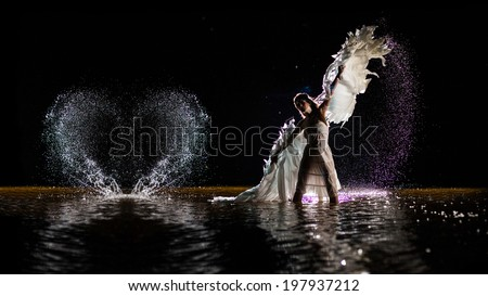 Beautiful dancing white angel is making heart from the water drops. - stock photo