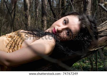 beautiful dark-haired girl lying on the hanging tree