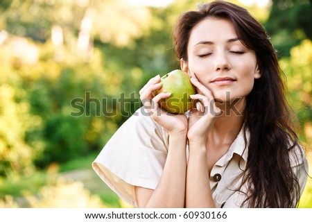 Beautiful dark-haired girl with apple, against green summer garden. - stock photo