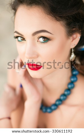 Beautiful dark-haired girl with red lips, beautiful makeup and big blue beads, closeup