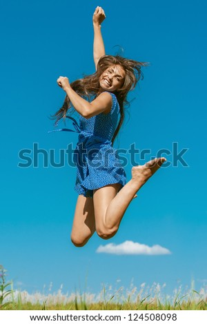 Beautiful dark-haired happy young woman jumping high in air, against background of summer blue sky.