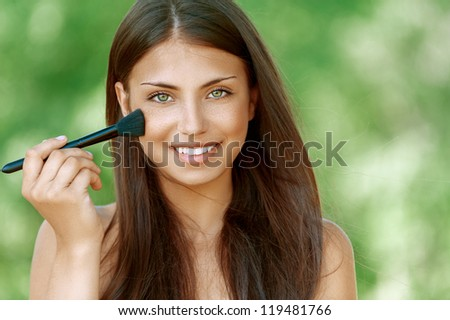 Beautiful dark-haired smiling young woman treats her face with brush, against background of summer green park. - stock photo