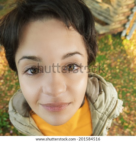 Beautiful dark-haired woman on earth covered with autumn fallen leaves. - stock photo