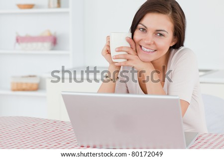 Beautiful dark-haired woman using her laptop and having a tea in her kitchen