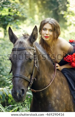 Beautiful dark haired women riding brown horse in summer park wearing long black dress decorated with flowers.