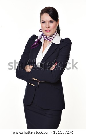 Beautiful dark haired young business woman dressed in a navy suit with a purple scarf and white shirt standing serious and intrigued and holding her arms crossed, isolated on white background - stock photo