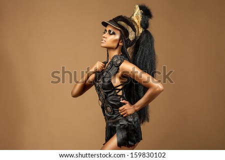 beautiful dark-skinned woman dressed in a military uniform Spartan force and ogres in her hands. - stock photo