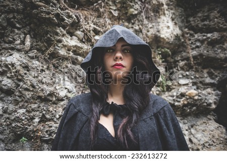 beautiful dark vampire woman with black mantle and hood halloween - stock photo
