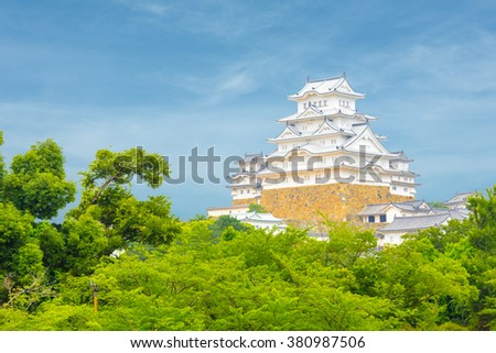 Beautiful daytime blue sky behind recently renovated Himeji-jo castle over the tops of trees seen from a distance in Himeji, Japan after 2015 renovations finished