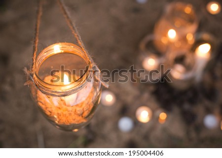 Beautiful decorated romantic place for a date with jars full of candles hanging on tree and standing on a sand. Copy Space - stock photo