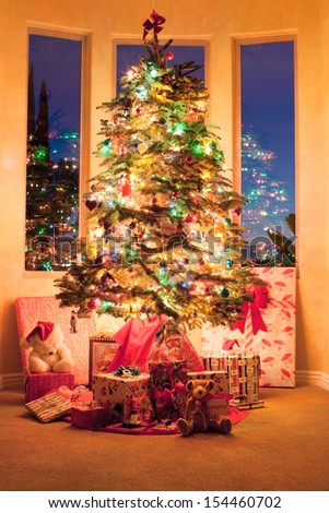 Beautiful decorated tree with gifts from Santa at sunrise on Xmas day - stock photo