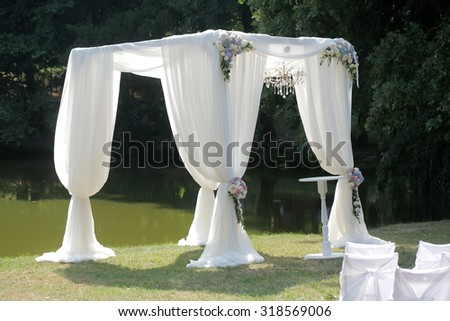 Beautiful decorated with light white fabric of chiffon one chandelier and bouquets of roses pastel colors pavilion and table standing on green grass near lake and trees sunny day, horizontal photo - stock photo