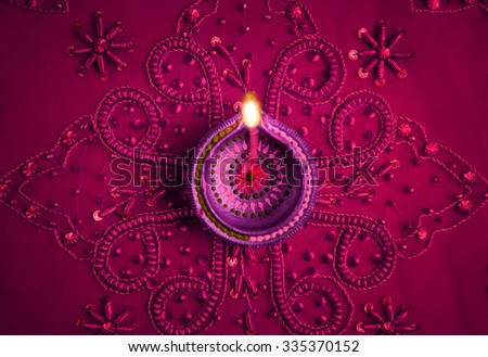 Beautiful decorative Diwali lamp on embellished purple background. Happy Diwali Greeting Card. - stock photo
