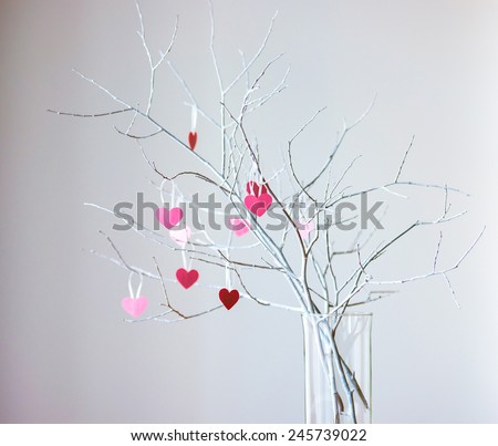 Beautiful decorative white branches with small valentine's hearts. Toned picture - stock photo