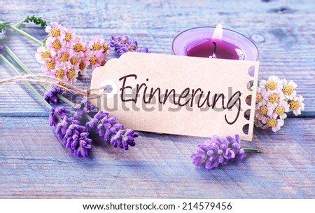 Beautiful delicate blue and lilac colored background depicting - Erinnerung - Memories - with fresh scented lavender spikes, dainty flowers and a burning aromatic candle on blue rustic wooden boards