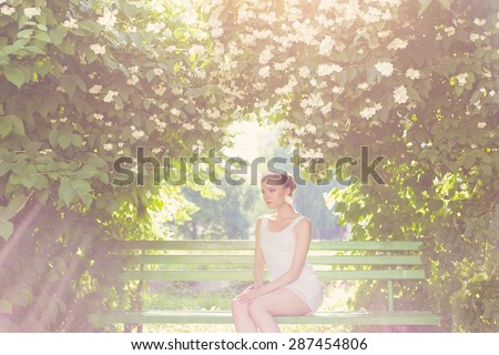 beautiful delicate elegant woman bride in white dress with hair and tiara on his head sitting in a lush garden on a bench under the jasmine in luchas sun , romantic toning - stock photo