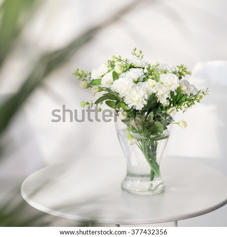 Beautiful delicate white flowers on the glass table - stock photo