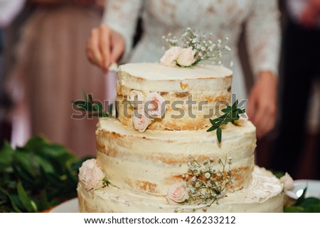 Beautiful delicious white wedding cake ceremony at the table - stock photo