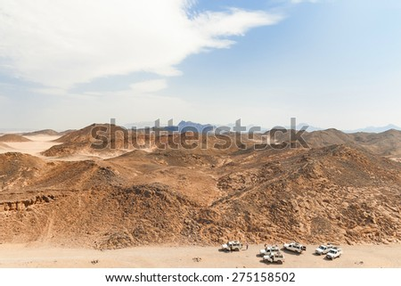 Beautiful Desert Landscape of Egypt. Safari cars go on the road between mountains. - stock photo