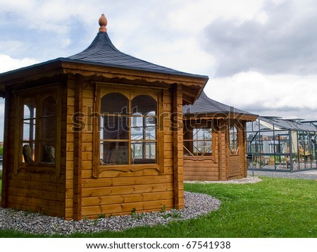 Beautiful design garden wood glass classical gazebo pavilion with furniture - stock photo