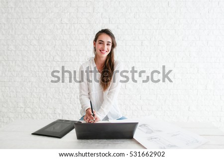 Beautiful designer working with devices, free space. Confident retoucher smiling at camera while sitting at workplace with laptop and graphic tablet. Art, business, creativity concept