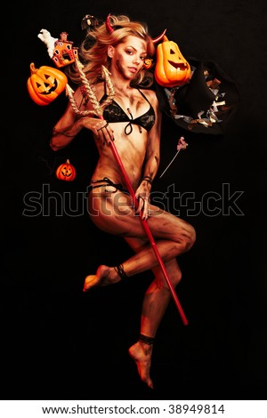 Beautiful devil with trident and Halloween accessories on black - stock photo