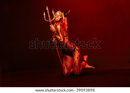Beautiful devil with trident  on black - stock photo