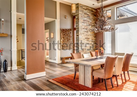 Beautiful Dining Room with Entryway, Table, Elegant Light Fixture in New Luxury Home - stock photo